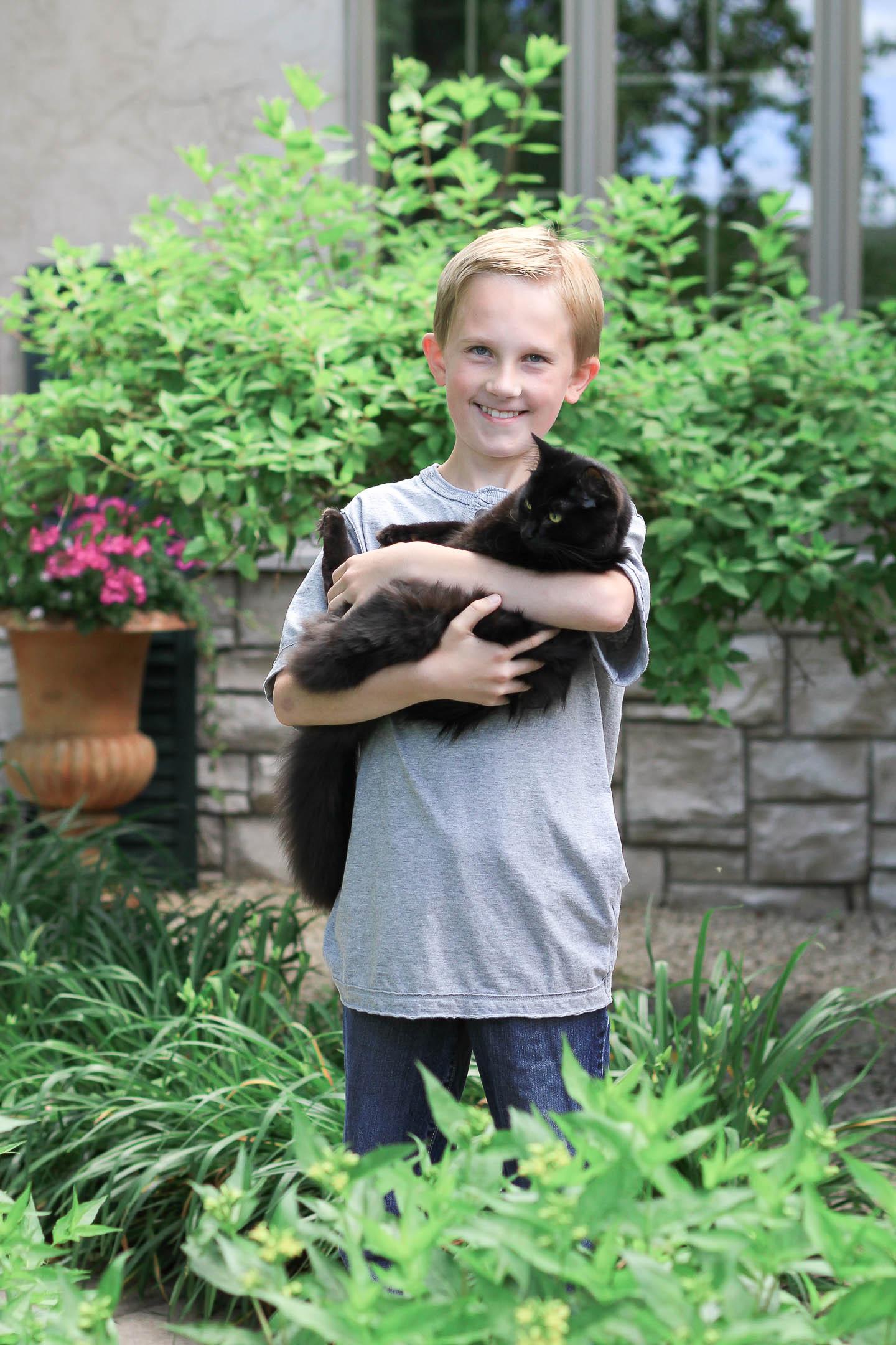 A boy holding a black cat