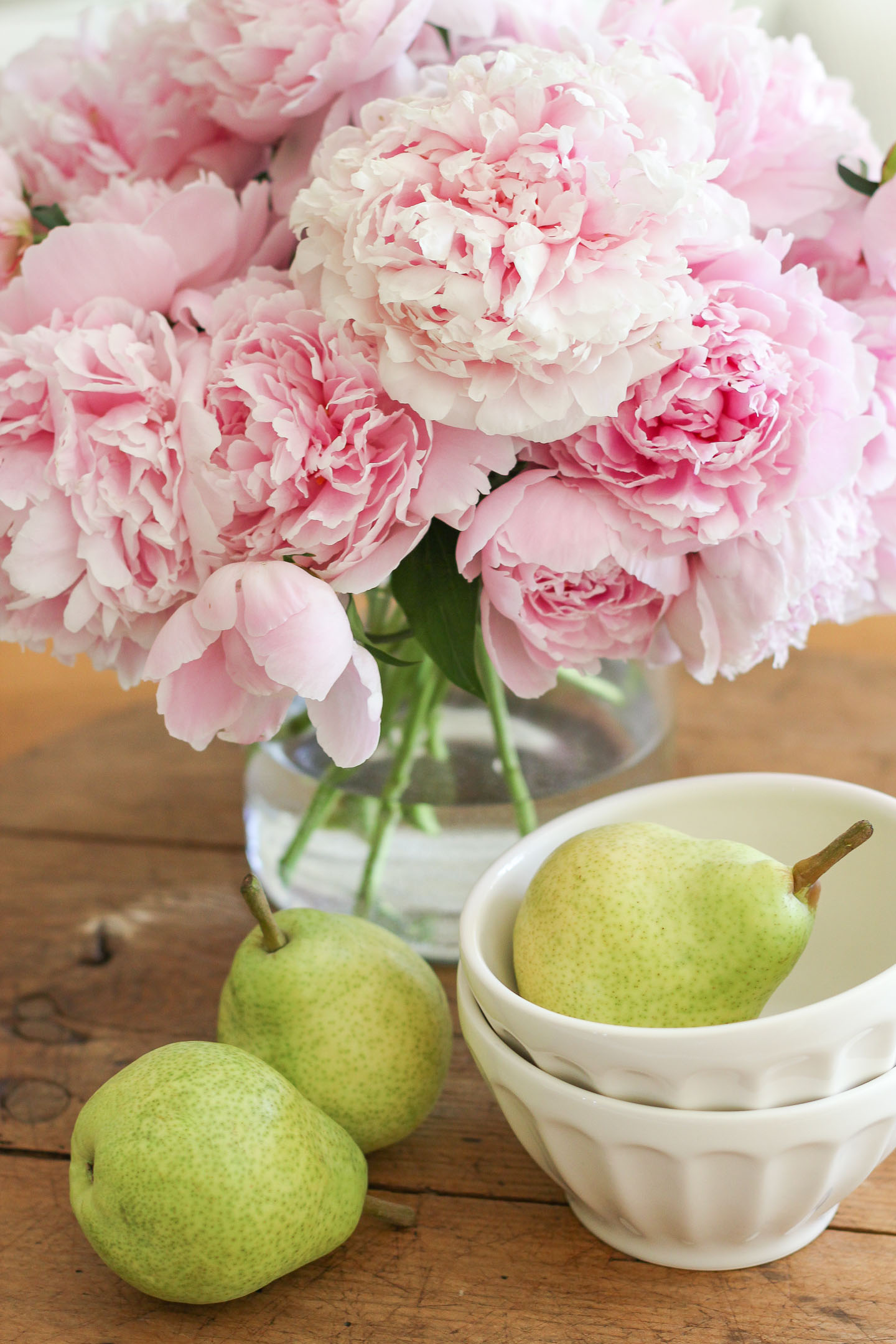 A bouquet of peonies and some pears in a bowl.