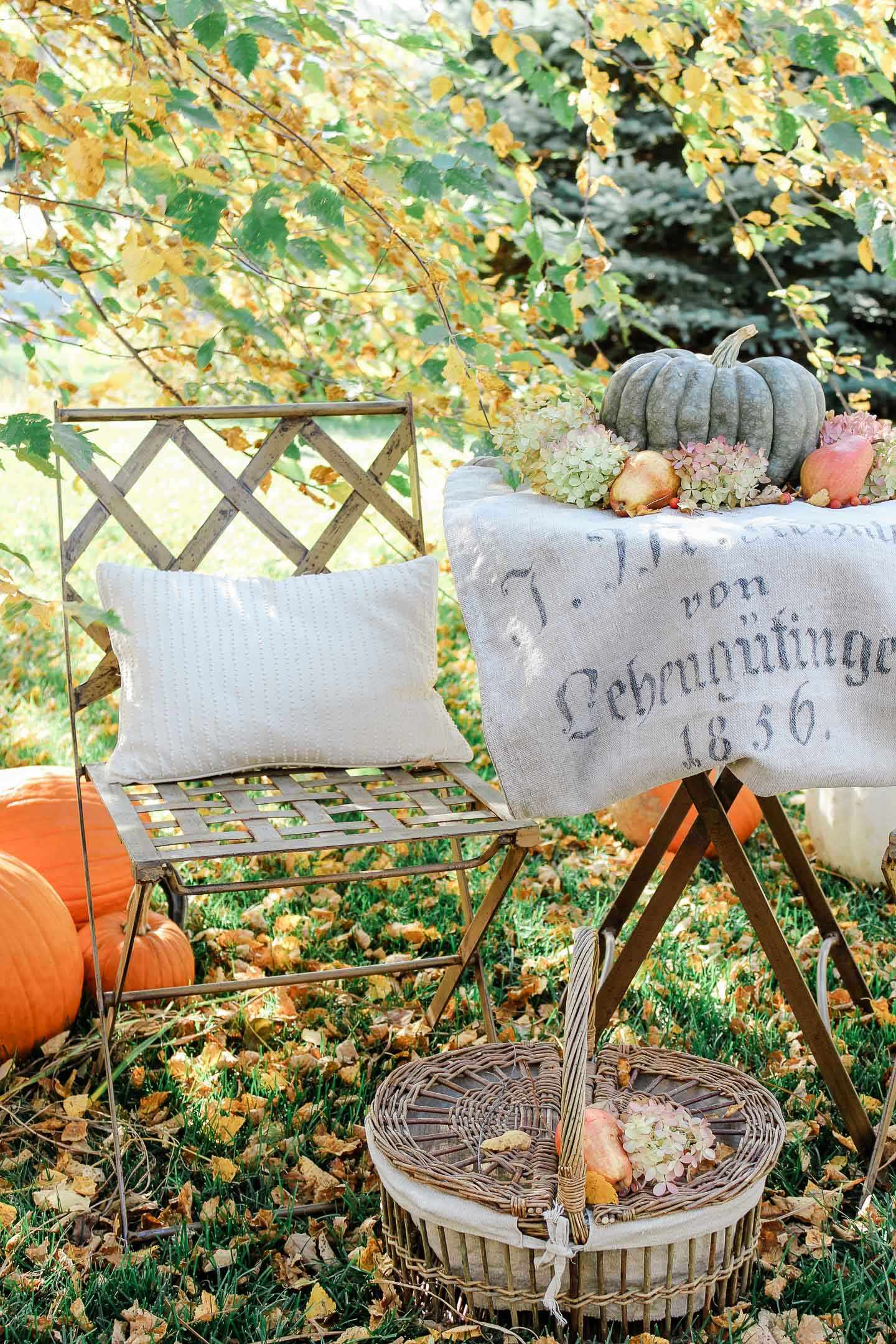 An outdoor table topped with a german grain sack, pumpkin, pears and flowers.