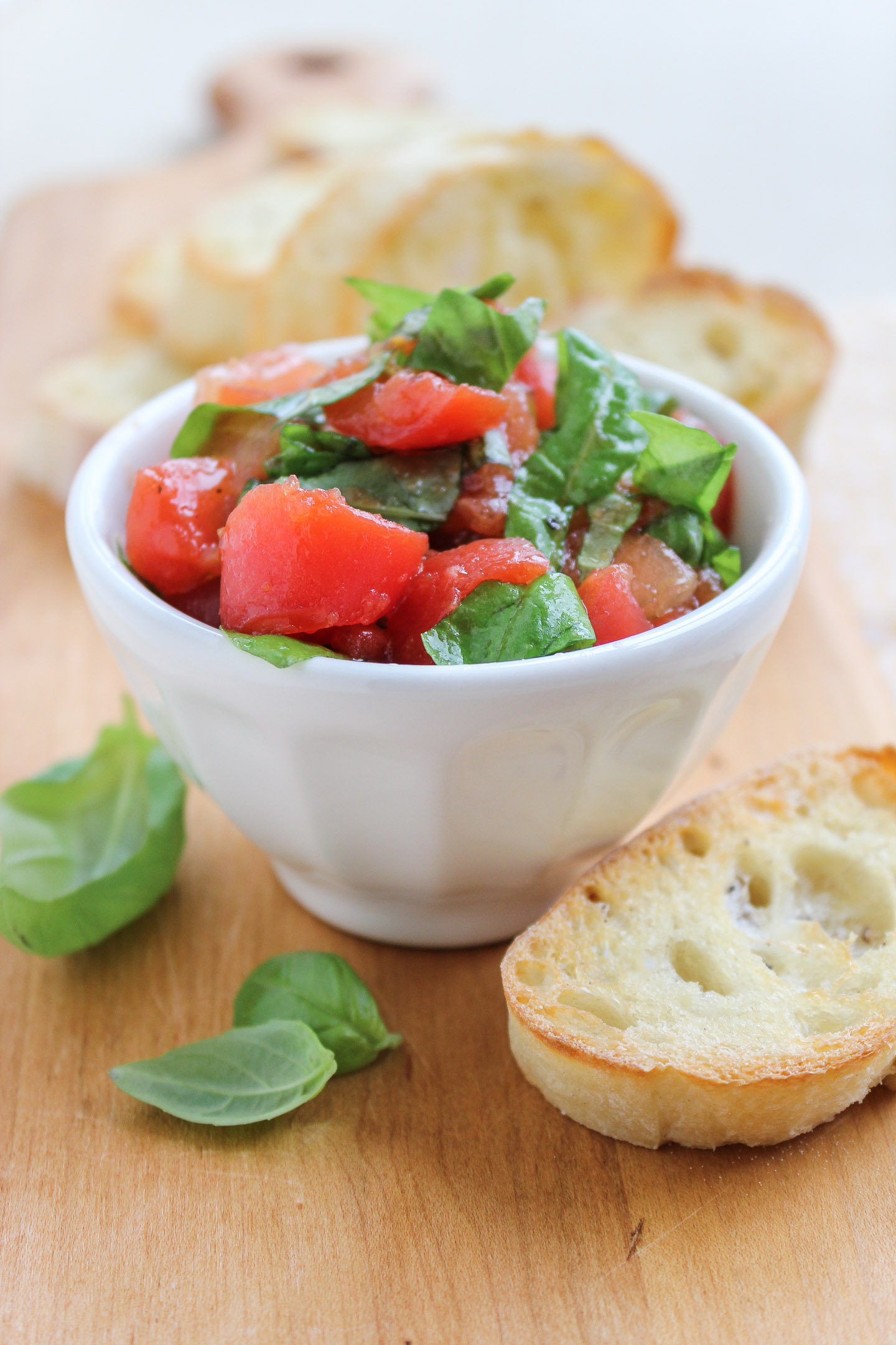 Bruschetta mixture...chopped tomatoes and basil in a bowl next to a slice of bread.