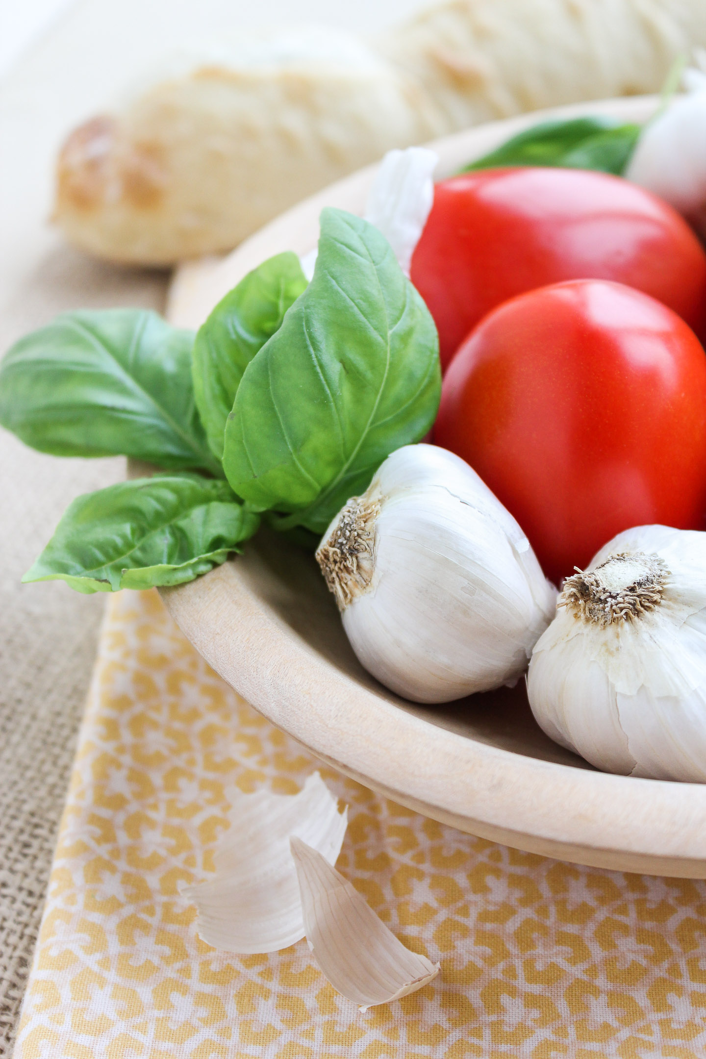 Tomatoes, basil and garlic in a bowl.