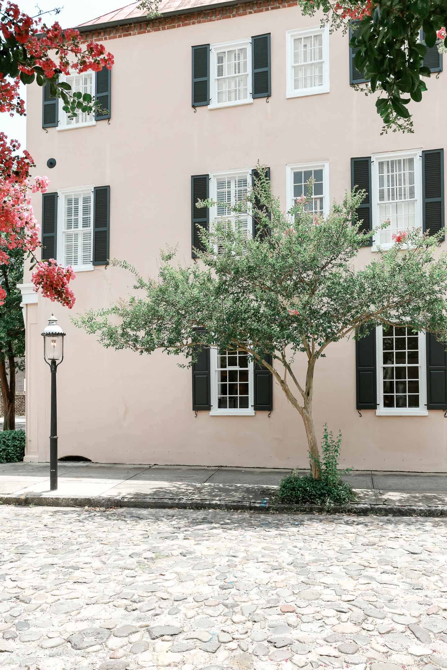 A pale pink building with black shutters located on a cobblestone street in Charleston.