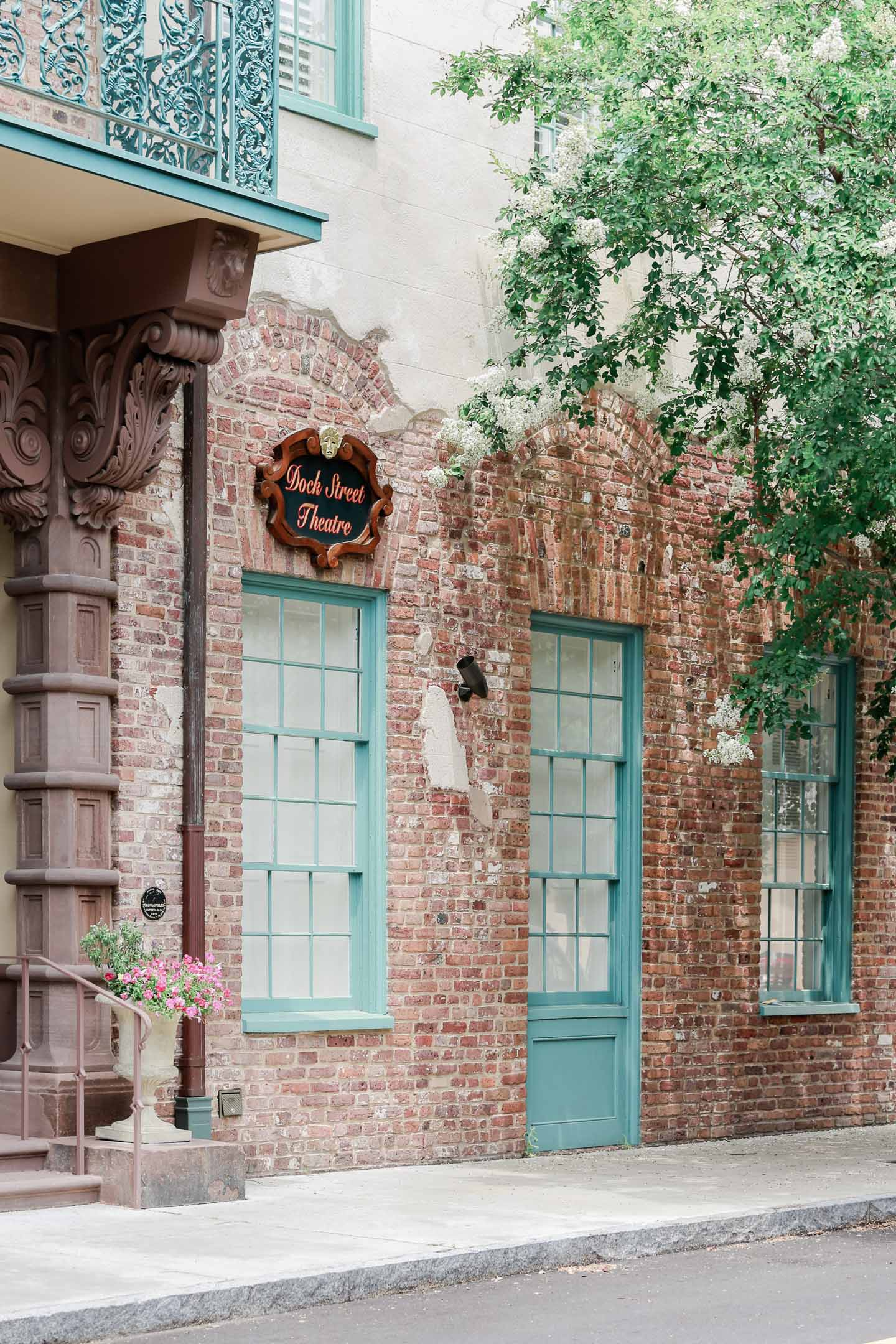 The Dock Street Theatre in Charleston is a brick building with turquoise windows and doors.