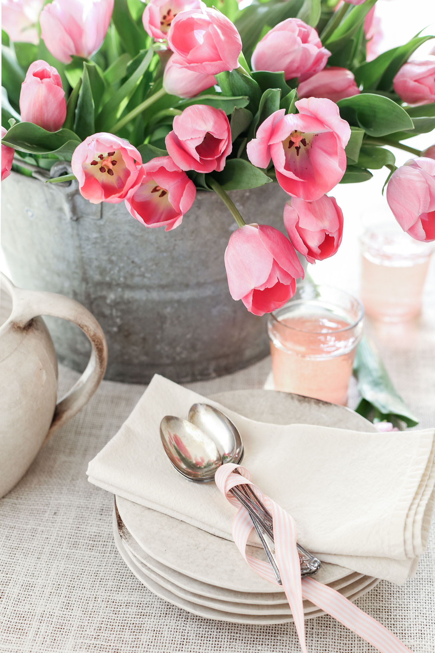 Pink tulips in a galvanized bucket on a table with plates and spoons.