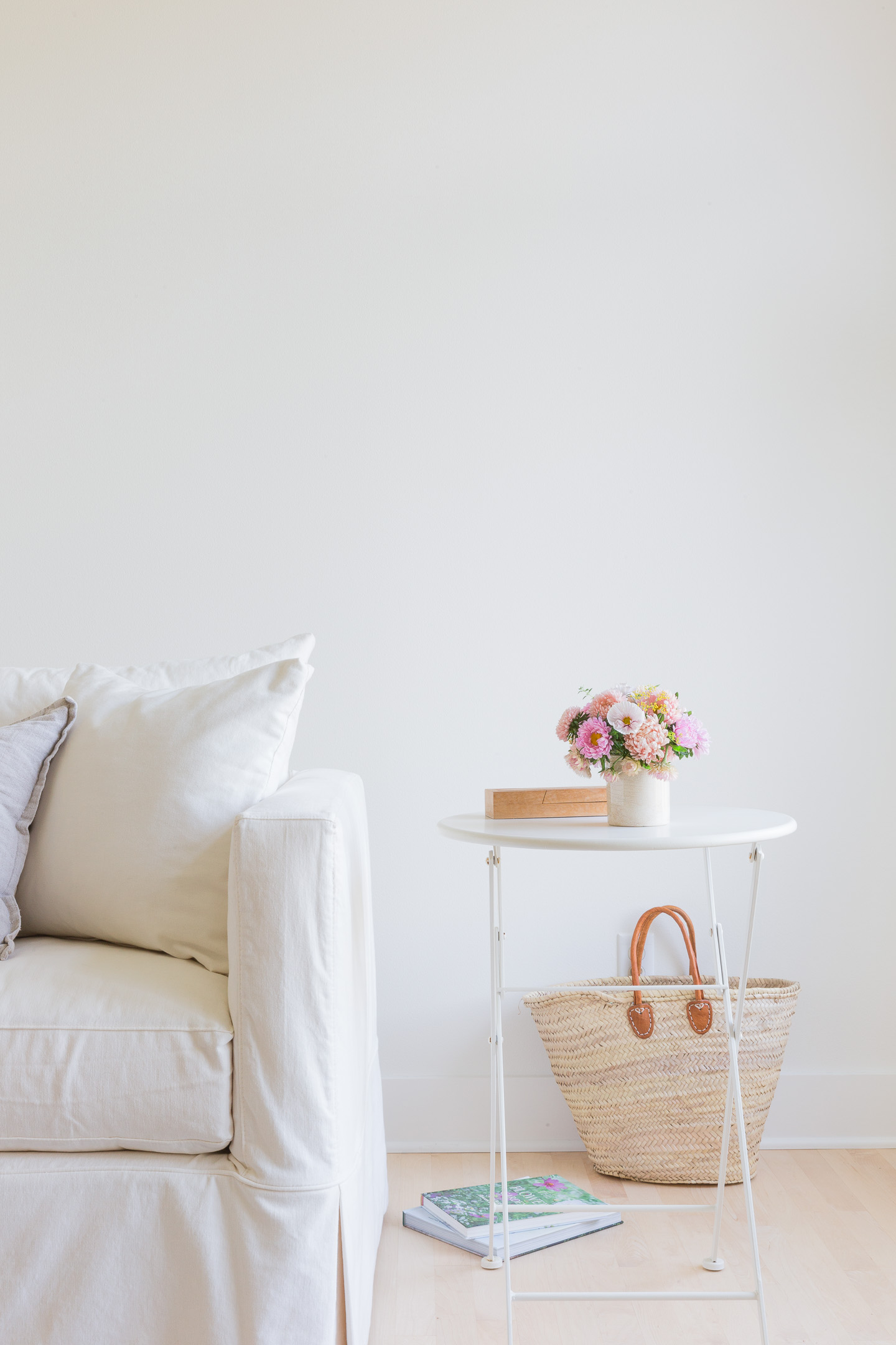 A small flower arrangement on a white table next to a white couch.