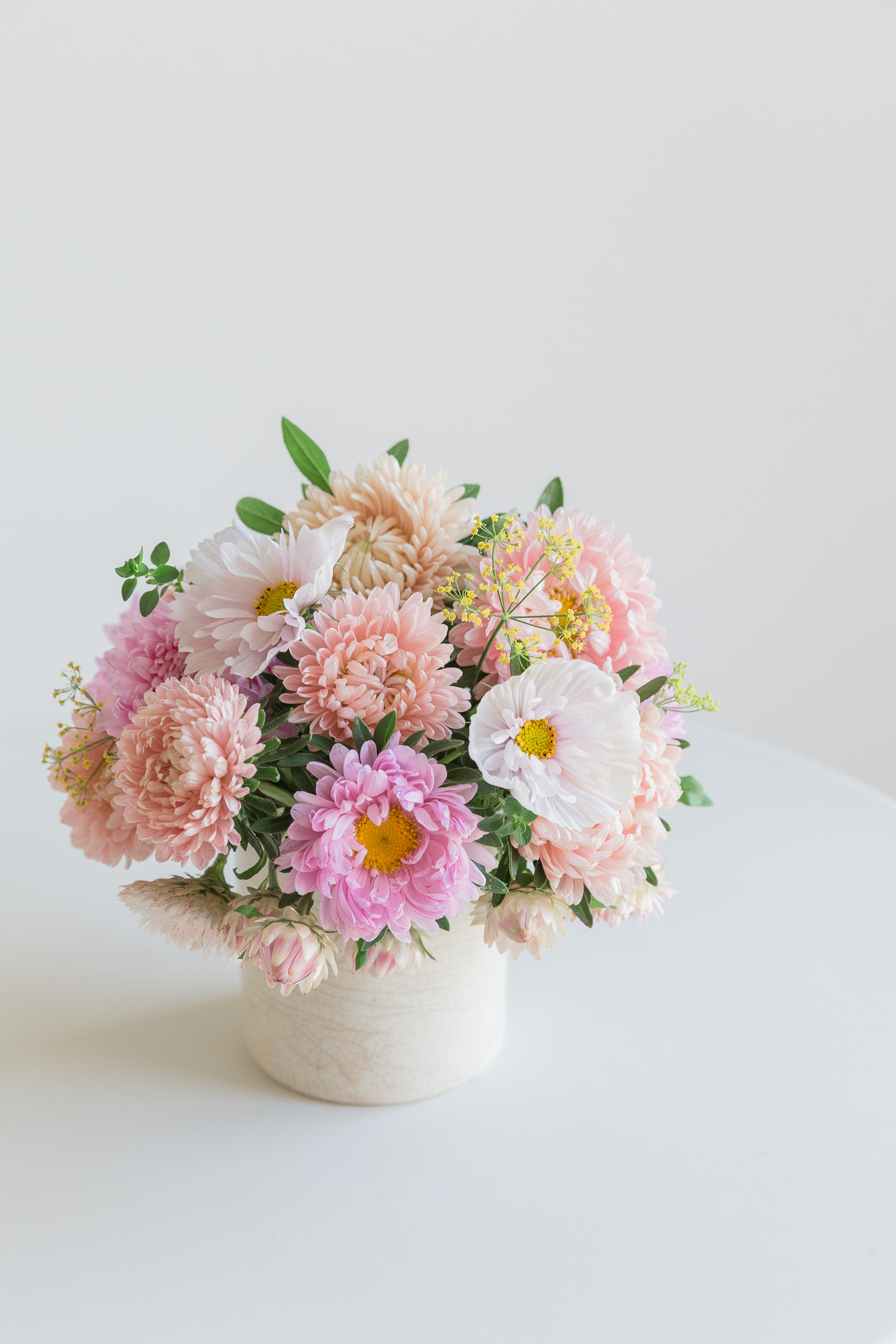 A flower arrangement containing China Asters, Cosmos, Strawflowers and Dill.