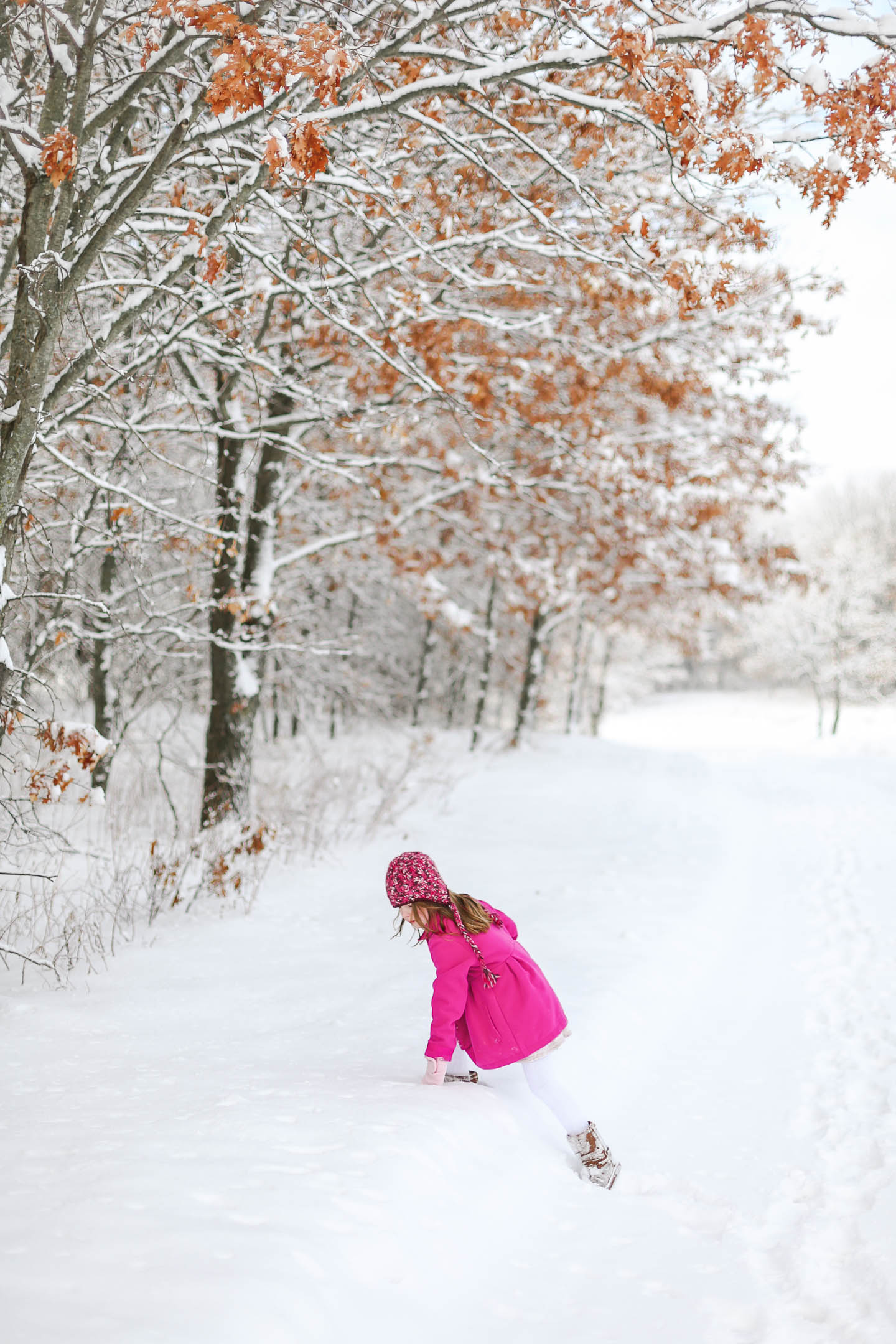 A little girl in a bright pink coat climbing up a snowbank.